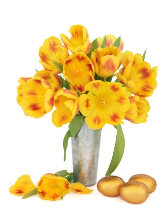 Yellow and red tulip flower arrangement in an aluminium vase with gold chocolate easter eggs over white background Stock Photo - 17248863