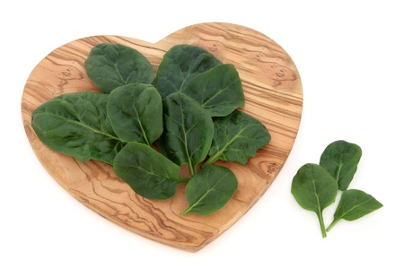 Spinach leaf sprigs on a heart shaped olive wood board over white background  Stock Photo - 17248866