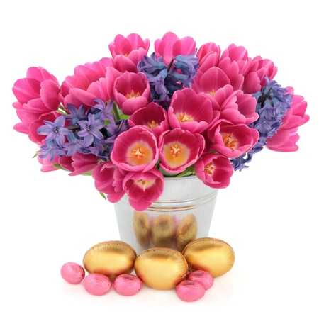 Tulip and hyacinth flower arrangement in a metal vase with chocolate easter egg group over white background  Stock Photo - 17248864