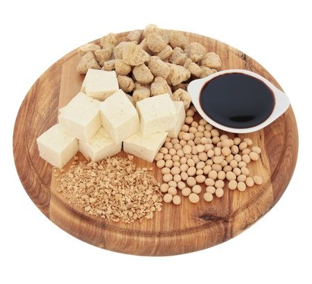 Soybean products of flakes, chunks, beans, sauce and tofu on a wooden board isolated over white background Stock Photo - 17420727