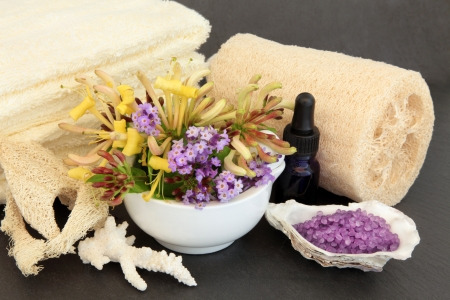 Honeysuckle and lavender flower blossom, cream  towels, exfoliating spa scrub, aromatherapy essential oil bottle, coral and oyster shell with bath pearls over slate Stock Photo - 17420730