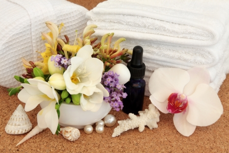 Spa beauty treatment accessories with orchid, honeysuckle, lavender herb and freesia flower blossom over cork background  photo