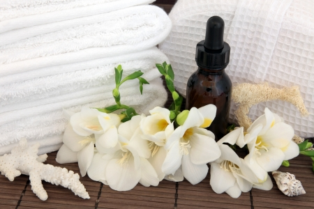 Spa arrangement of freesia flower blossom, aromatherapy essential oil bottle, white towels and linen covered,sponge, exfoliating scrub and sea shells over bamboo  Stock Photo - 17420716