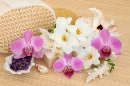 Spa still life arrangement of freesia and orchid flower blossom,  bath salts, soap, sea shells and exfoliating sponges over bamboo   Stock Photo - 17420728