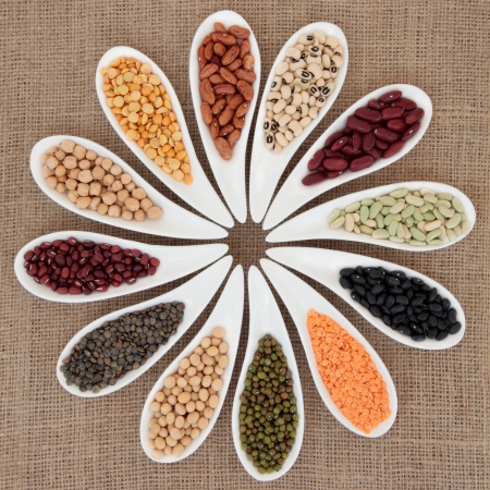 mung: Pulses vegetable selection of peas, beans and lentils in white porcelain bowls over hessian background