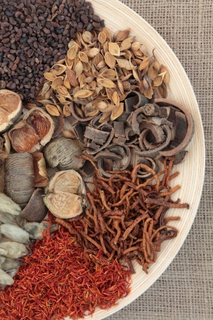 Chinese traditional herbal medicine selection on a round wooden bowl over hessian background Stock Photo - 17420744