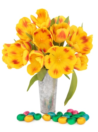 Chocolate easter egg group with red and yellow striped tulip flower arrangement in an aluminium vase over white background  Stock Photo - 17420723
