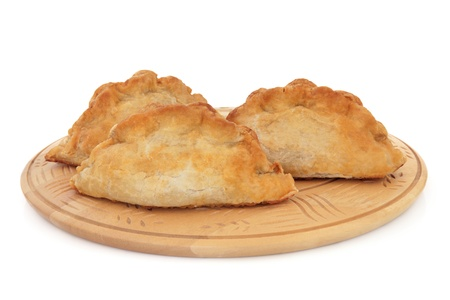 Cornish pasties on a beech wood board over white background  Stock Photo - 17588042