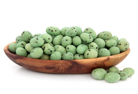 Wasabi peanuts in an olive wood bowl over white background Stock Photo - 17588055