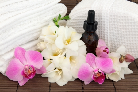Spa and aromatherapy beauty treatment accessories with pink orchid and white freesia flower blossom over bamboo background Stock Photo - 17588060