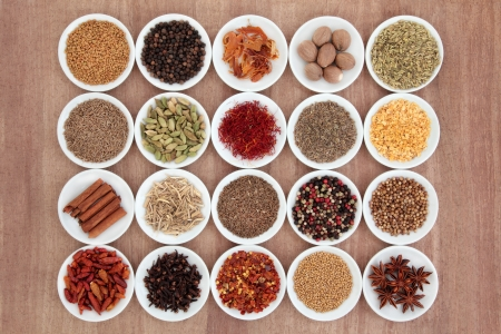 Large spice and herb selection in white porcelain bowls over papyrus background  Stock Photo - 17588066