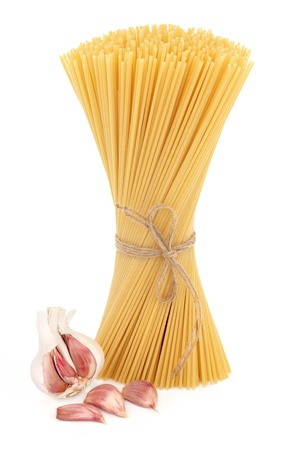 Spaghetti pasta tied in a bundle with garlic clove bulb over white background  Stock Photo - 17588045