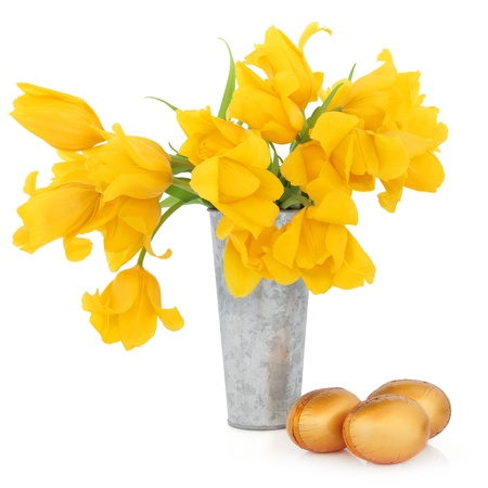 Yellow tulip flower arrangement in an aluminium vase with gold chocolate easter eggs over white background  Stock Photo - 17588039