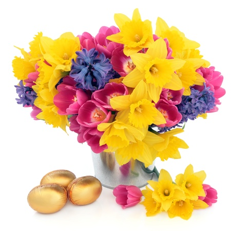 Tulip, daffodil and hyacinth flower arrangement in a metal vase with chocolate golden easter egg group over white background  Stock Photo - 17588044