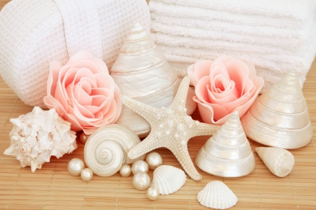 Bathroom accessories of rose soap petal buds, sea shells, pearls with white towel stack and linen sponge over bamboo background Stock Photo - 17588046