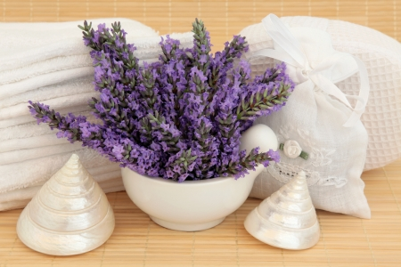Lavender herb flower sprigs, spa accessories and mother of pearl sea shells over bamboo background  photo