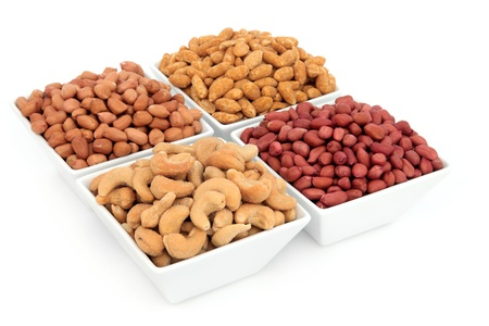 Peanut, redskin, roasted and cashew nuts in porcelain bowls over white background Stock Photo - 17699499