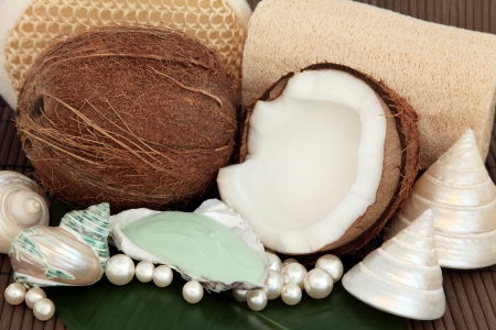 Coconut spa products with moisturiser, exfoliating scrubs, sea shells and pearls over bamboo background Stock Photo - 17699501