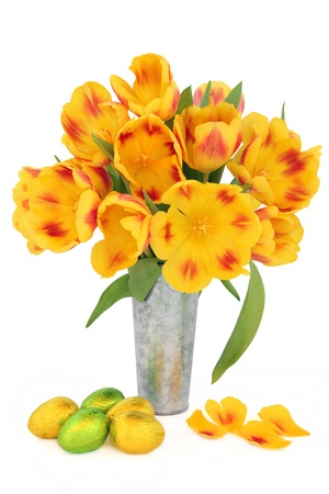 Easter egg group and red and yellow striped tulip flower arrangement in an aluminium vase over white background Stock Photo - 17699498