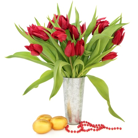 Tulip flower arrangement in a metal vase with gold easter egg group and red bead chain over white background Stock Photo - 17699491