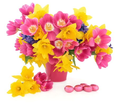 Tulip, daffodil and hyacinth flower arrangement in a pink vase with a chocolate easter egg group over white background Stock Photo - 17699497