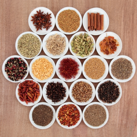 Large herb and spice selection in white porcelain bowls over papyrus background  photo