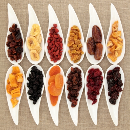 Dried fruit selection in porcelain dishes over beige linen background  photo