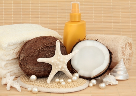 exfoliate: Coconut spa accessories with sunscreen bottle, shells, towels, exfoliating scrub over bamboo background
