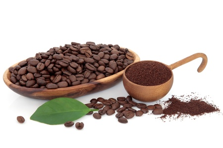 Coffee beans ground and whole with leaf sprig over white background  Stock Photo - 17817724