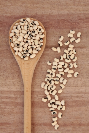 Black eyed pea pulses in a wooden spoon over papyrus background  Stock Photo - 17817732