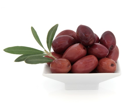 kalamata: Black olives in a porcelain bowl with leaf sprigs over white background  Stock Photo