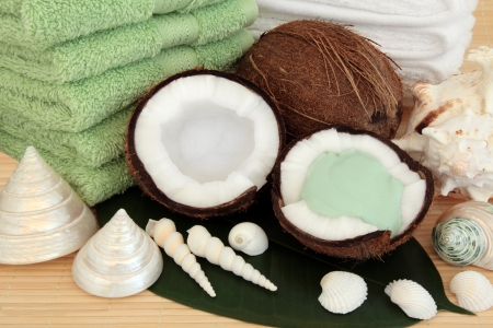 Coconut fruit and spa products with moisturising cream, towels and sea shells over bamboo and leaf background Stock Photo - 18020701