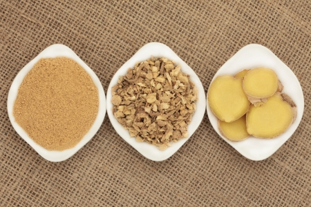 Ginger powder, root and fresh slices in white porcelain dishes over hessian background Stock Photo - 18020126