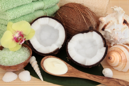 Coconut spa products with body moisturiser, green bath salts, exfoliating scrub, towels and sea shells over bamboo and leaf background Stock Photo - 18032478