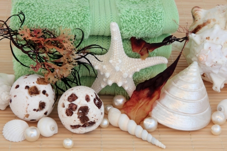 Seaweed spa accessories with bath bombs, towels, sea shells and pearls over bamboo background  Stock Photo - 18032484
