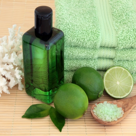 Lime fruit with spa accessories of green towels, bubble bath, sea salt and coral shell over bamboo background  Stock Photo - 18032481