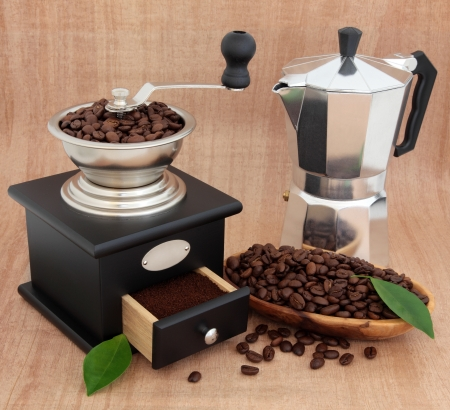 percolator: Coffee grinder, espresso percolator, beans and leaf sprigs over papyrus background  Stock Photo