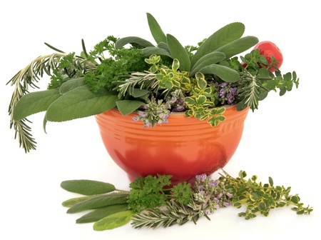 Parsley, sage, rosemary and thyme herb  leaf and flower sprigs in a red mortar with pestle over white background  Stock Photo - 18032491