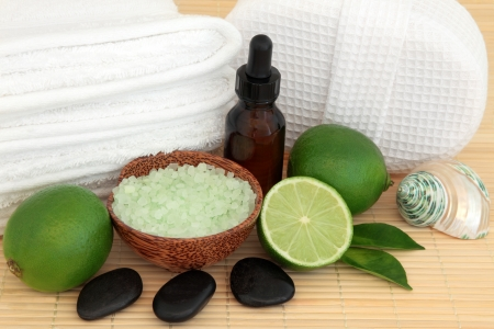 Spa and aromatherapy accessories with lime fruit halves over bamboo background  Stock Photo - 18305440