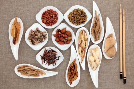 medicinal herb: Chinese herbal medicine in white porcelain bowls with chopsticks over beige linen background  Stock Photo