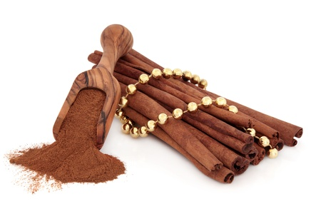Cinnamon sticks and powder in an olive wood scoop with gold bead chain over white background  Stock Photo - 18305436