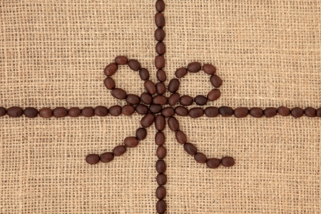 Coffee bean abstract design with central bow over hessian background  Stock Photo - 18305452
