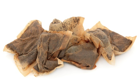 Used tea bag pile over white background  photo