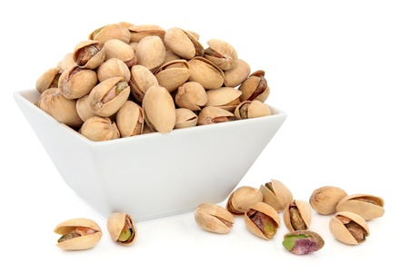 Pistachio nuts in porcelain dish over white background  Stock Photo - 18422903