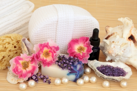Spa and aromatherapy accessories with rose and lavender herb flower sprigs, over bamboo Stock Photo - 18424170