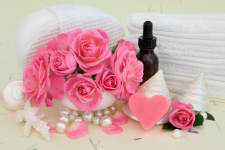 Rose flower arrangement with spa and aromatherapy accessories over mottled cream background  photo