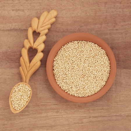 Quinoa grain in a terracotta bowl and wooden spoon over papyrus background Stock Photo - 18424167