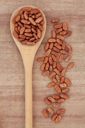 Pinto bean pulses in a wooden spoon over papyrus background  Stock Photo - 18422910