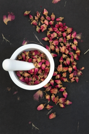 Rosebud flower heads in a white mortar with pestle over rose impregnated black paper, used in chinese herbal medicine  Stock Photo - 18422908