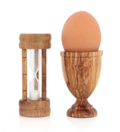 Olive wood timer and eggcup with brown speckled egg over white background  Stock Photo - 18424155